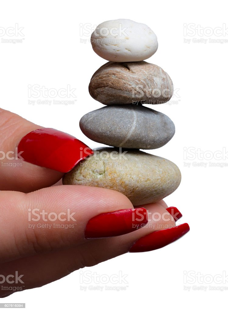 Woman balancing small stone zen tower in her hand stock photo