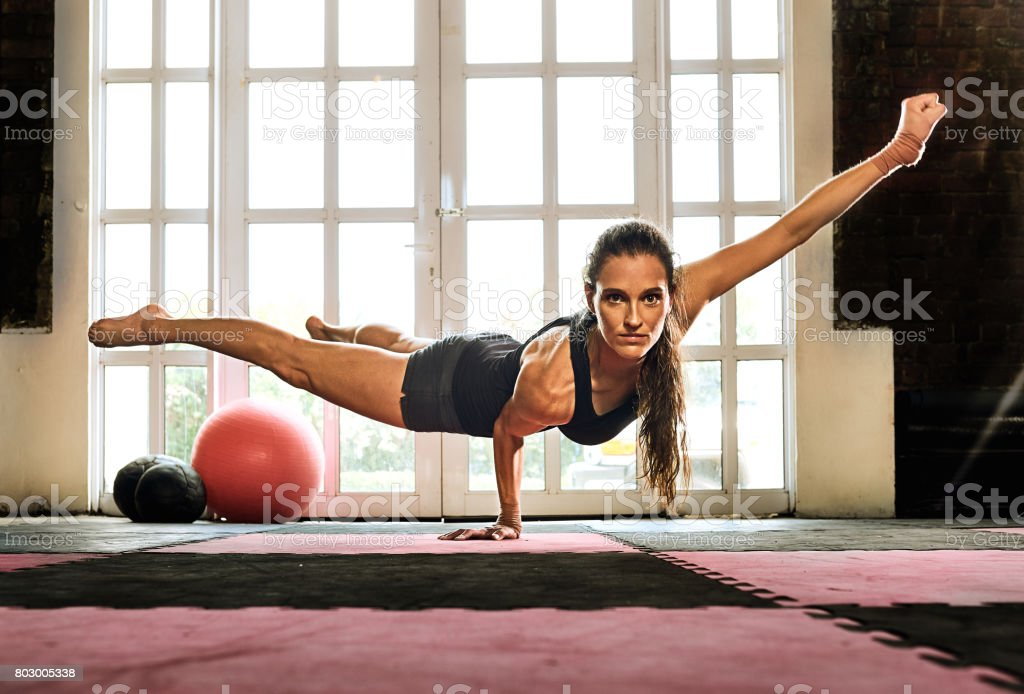 woman balancing while doing a one hand push up showing strength and determination stock photo