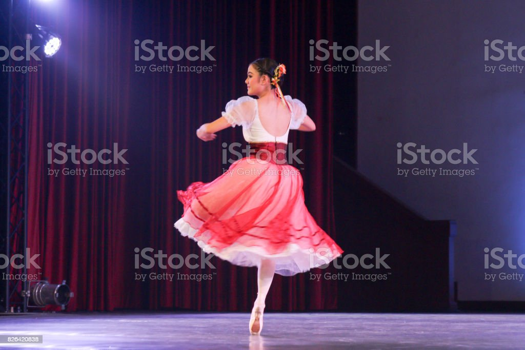woman ballerina who wear romantic tutu costume on stage turn with...