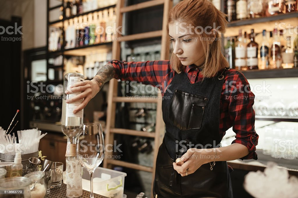 Woman bartender making an alcohol cocktail at the bar royalty-free stock photo