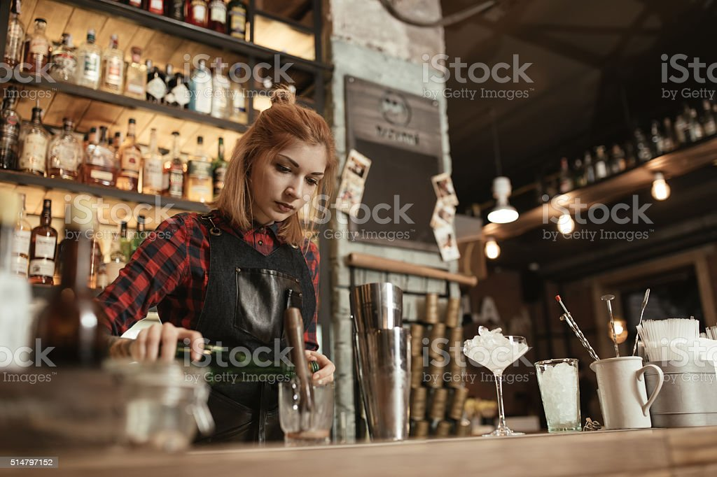 Woman bartender making an alcohol cocktail at the bar stock photo