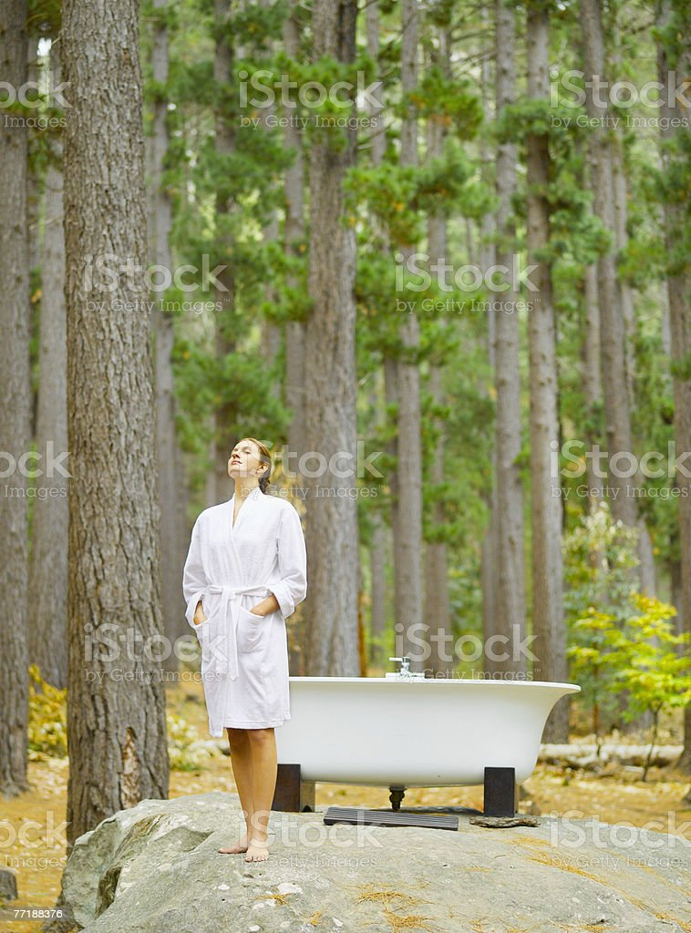 A woman before bathing outdoors in the woods stock photo