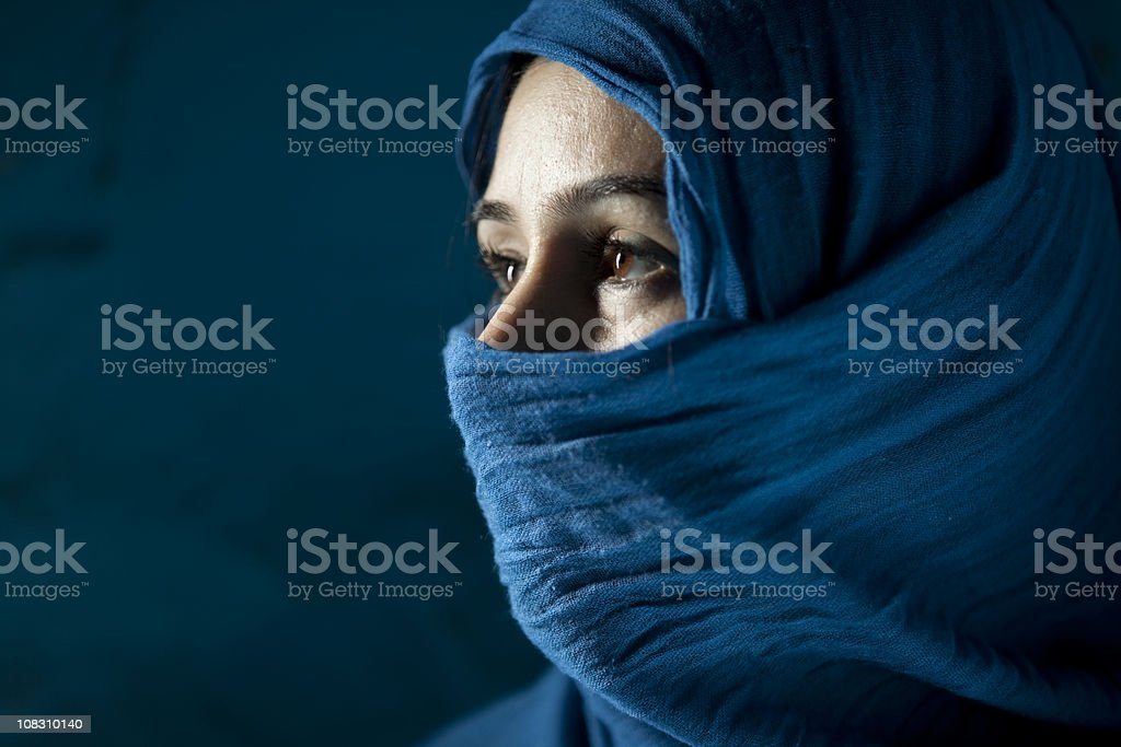 Woman Behind Blue Veil On Blue Background stock photo