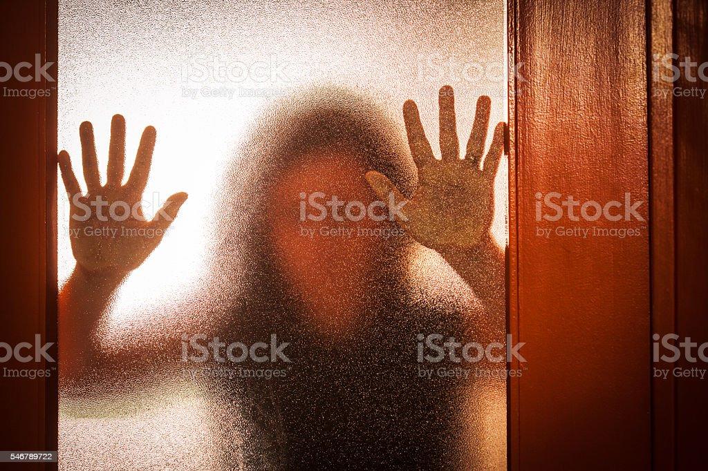 Woman Behind Glass Door stock photo