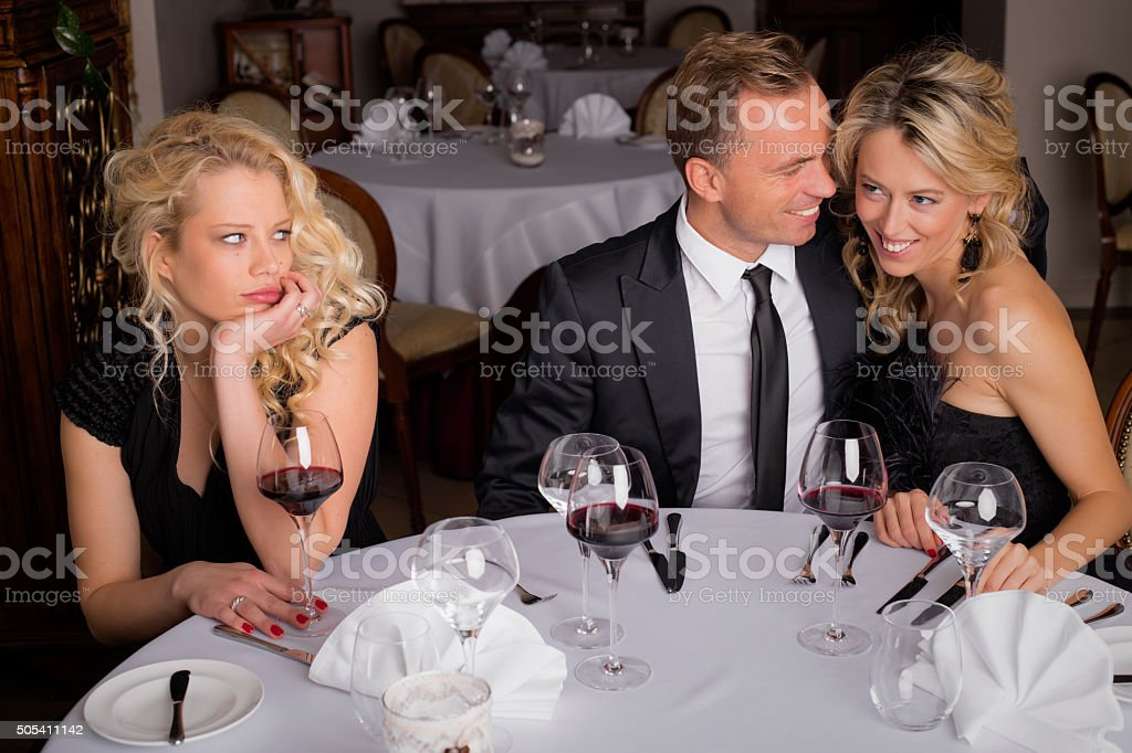 Woman being bored while having dinner with couple stock photo