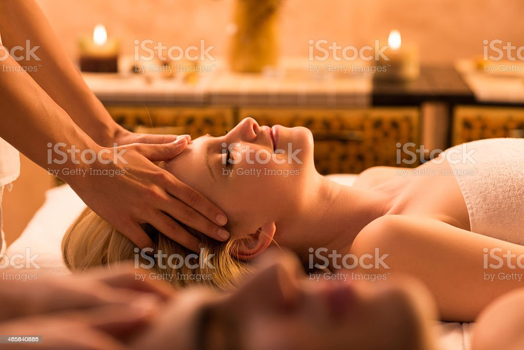 Woman being given a head massage in spa stock photo