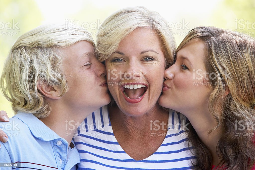 Woman Being Kissed By Her Teenage Children royalty-free stock photo