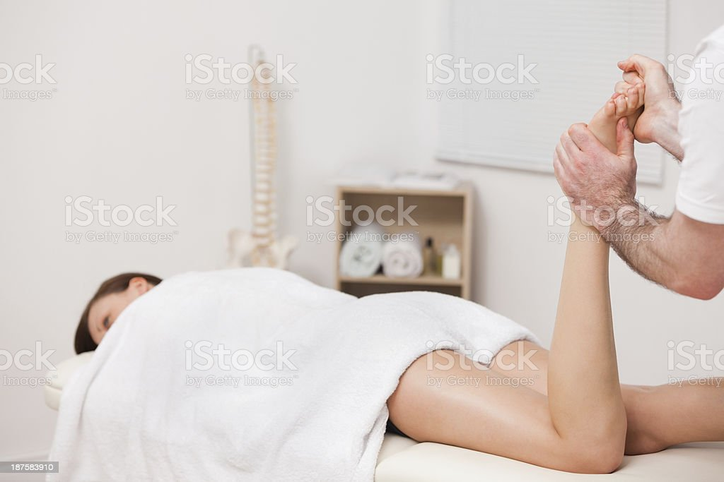 Woman being massaged her foot by a podiatrist royalty-free stock photo