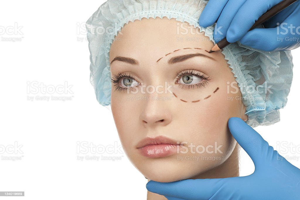 Woman being prepared for eye plastic surgery by blue gloves royalty-free stock photo
