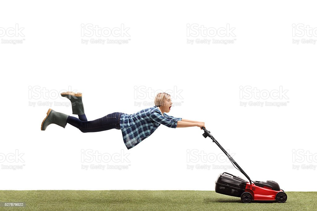 Woman being pulled by a lawnmower stock photo
