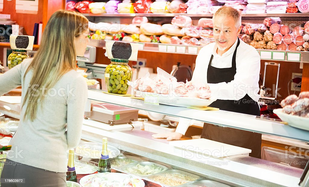 Woman being served in a delicatessen royalty-free stock photo