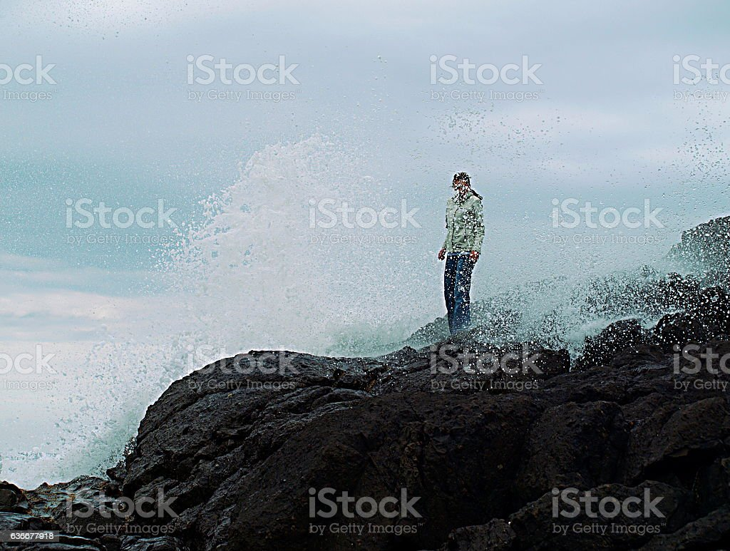 Woman being splashed by rogue wave in Tofino, British Columbia stock photo