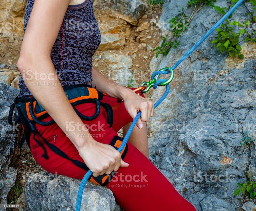 Woman belays climber in mountain closeup stock photo