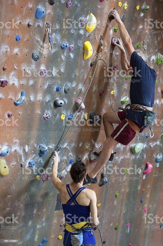 Woman Belays for Senior Man Doing Indoor Rock Climbing stock photo