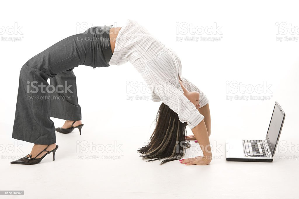 Woman bending backwards to look at a laptop stock photo