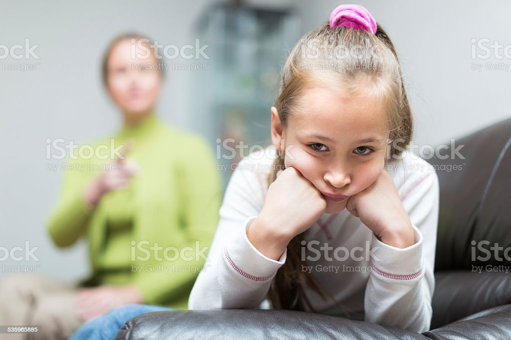 Woman berating daughter in home stock photo