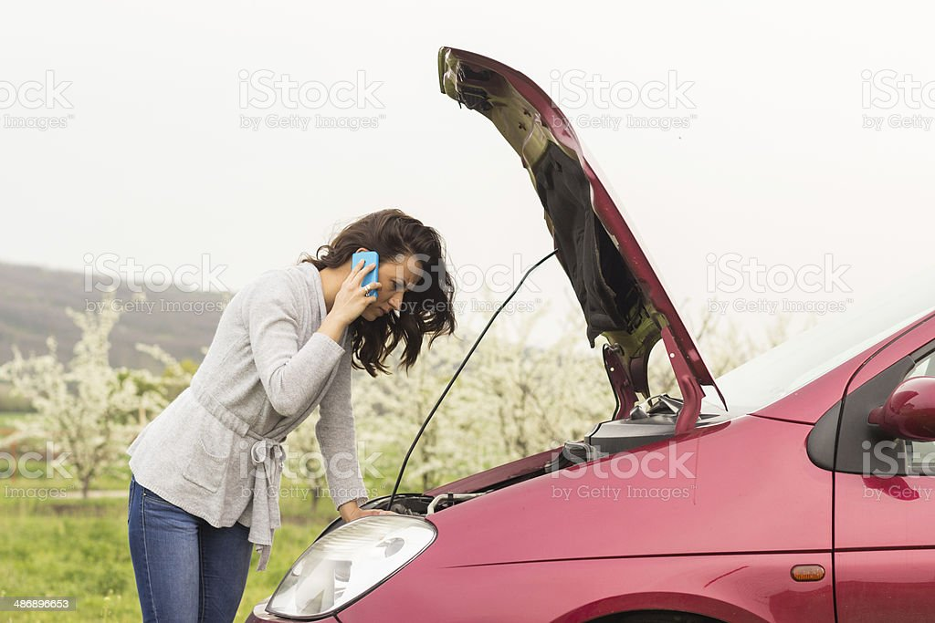 Woman besides her broken car talking on the cell phone stock photo