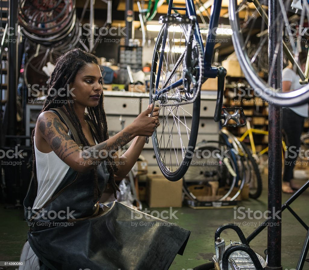 Woman bicycle mechanic fixing a wheel in a repair workshop stock photo