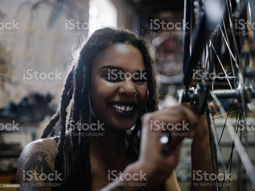 Woman bicycle mechanic with dreadlocks working in bike repair wo stock photo