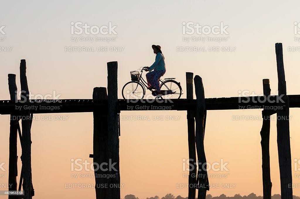 Woman bicycling across U Bein Bridge in Amarapura, Myanmar (sunset) stock photo