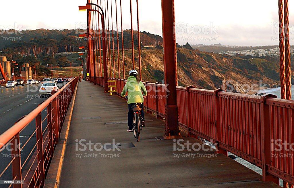 Woman biking over Golden Gate Bridge in San Francisco stock photo