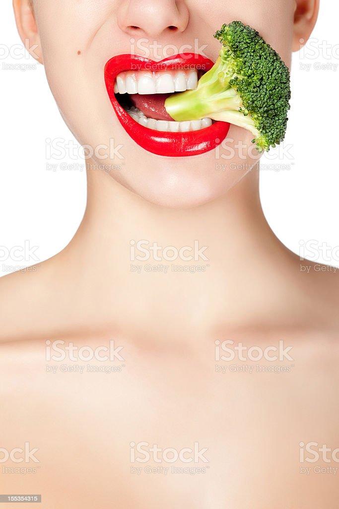 Woman biting broccoli stock photo
