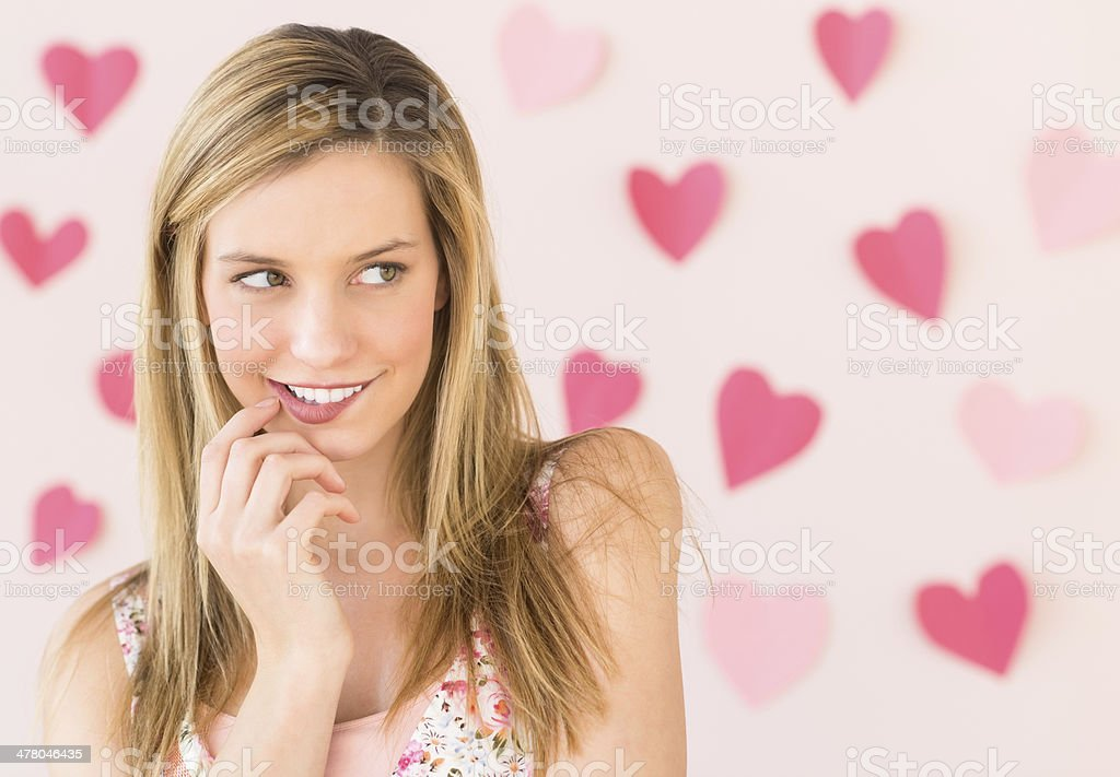 Woman Biting Lip With Heart Shaped Papers Against Colored Backgr stock photo