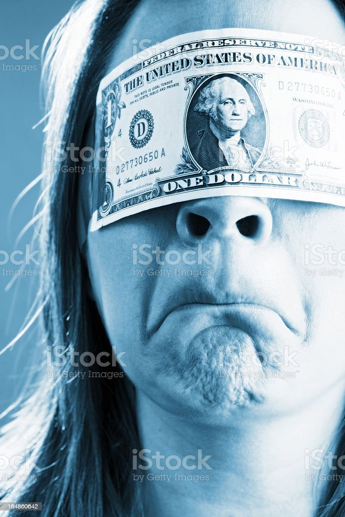 Woman blindfolded by dollar bill looks angry stock photo
