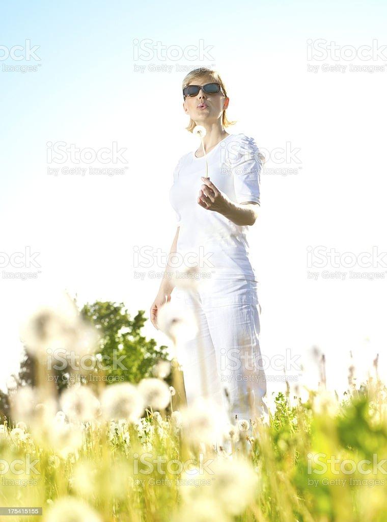 Woman blowing a dandelion on fields royalty-free stock photo