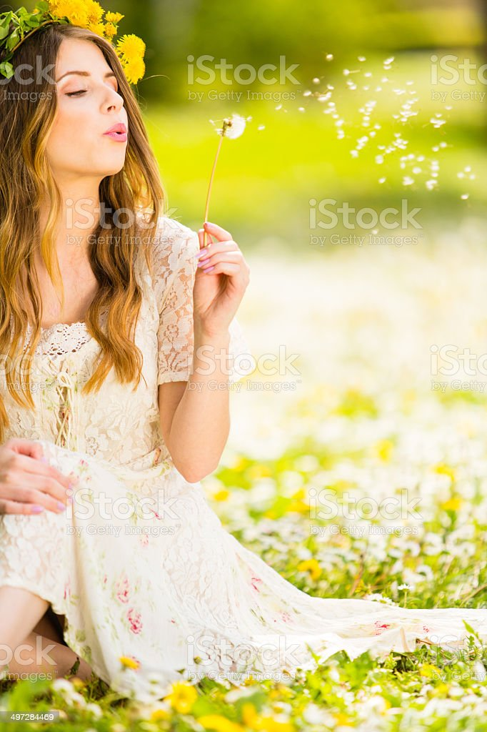 Woman blowing a dandelion stock photo