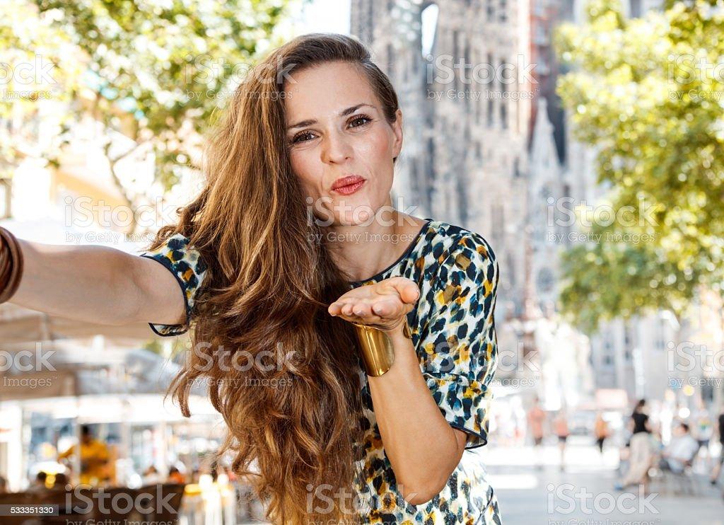 Woman blowing air kiss and taking selfie near Sagrada Familia stock photo