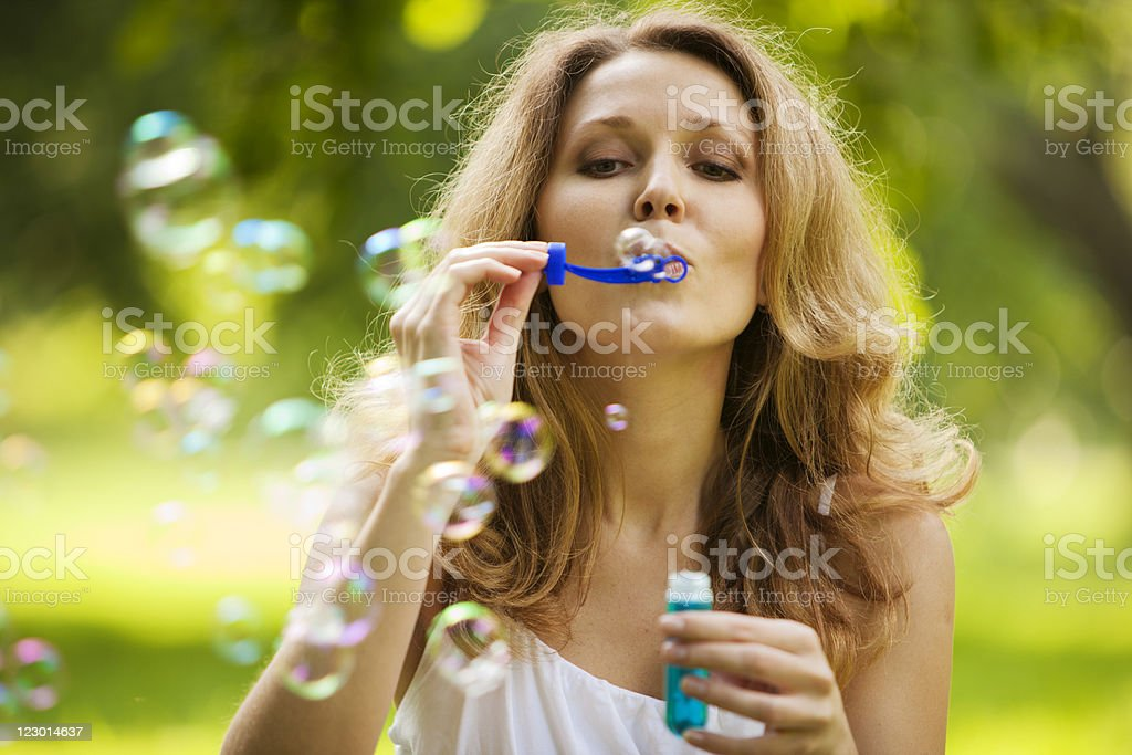 Woman blowing bubbles in park royalty-free stock photo