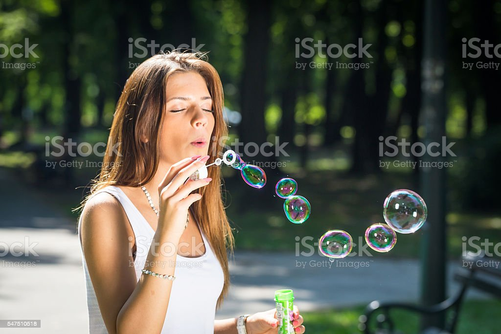 woman  blowing bubbles stock photo