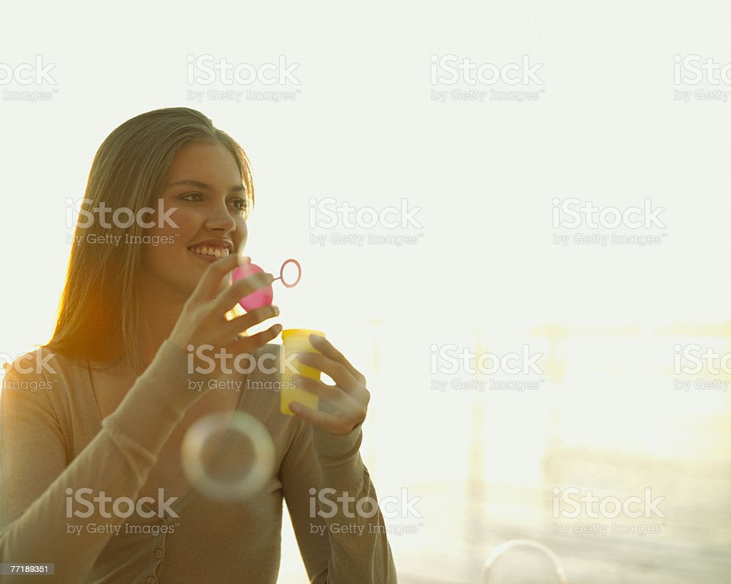 A woman blowing bubbles royalty-free stock photo