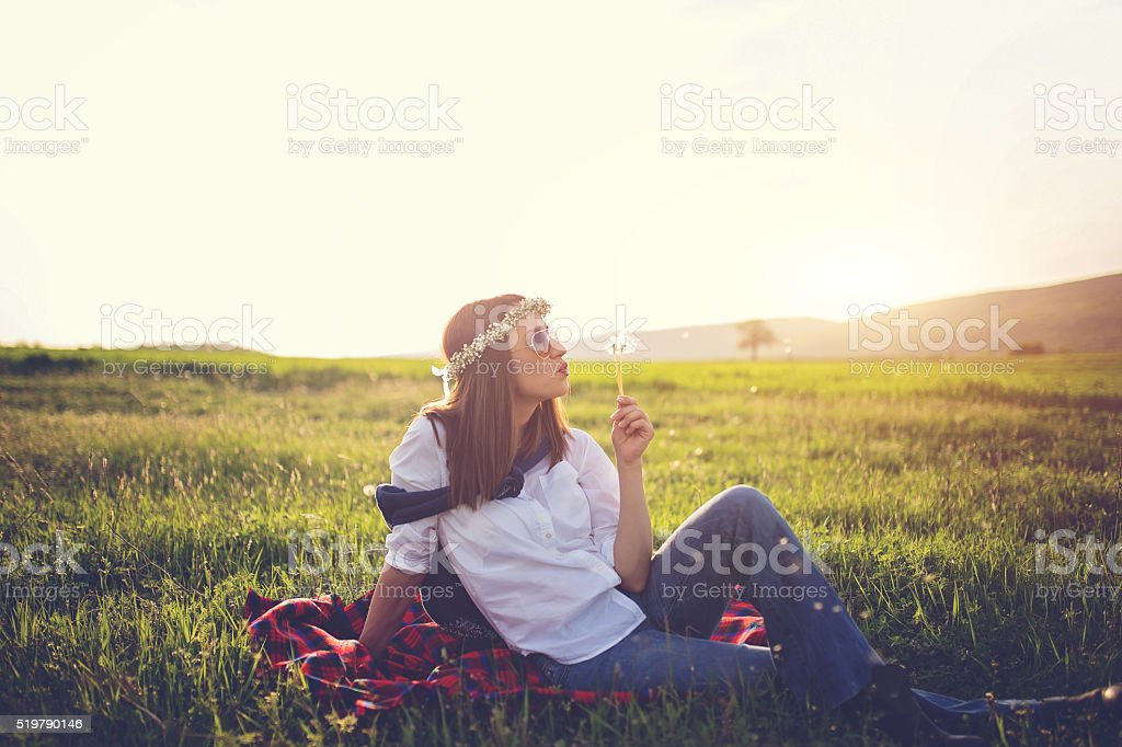 Woman blowing dadelion on a green field stock photo
