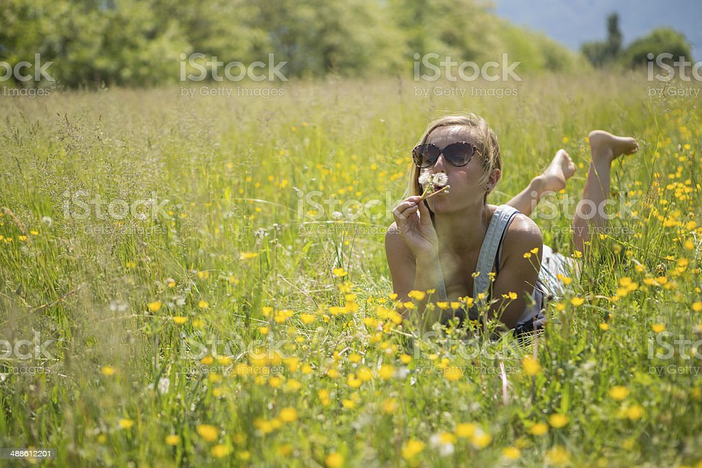 Woman blowing Dadelion seeds in the field royalty-free stock photo