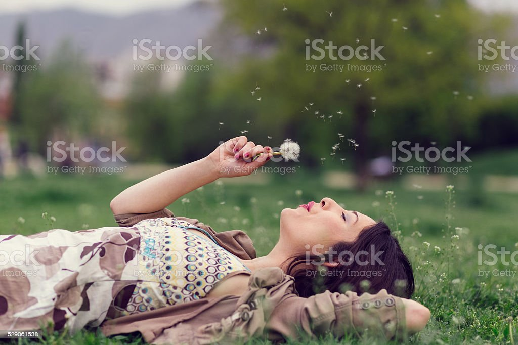 Woman blowing dandelion in the park with copyspace stock photo