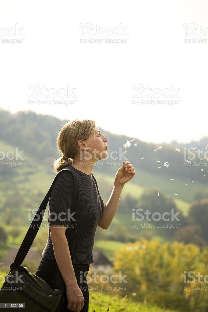 Woman blowing Dandelion royalty-free stock photo
