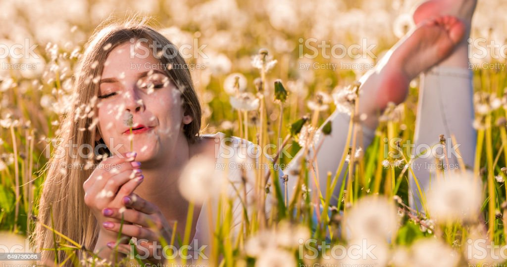 Woman blowing dandelion while lying on field stock photo