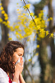 Woman blowing her nose in the park