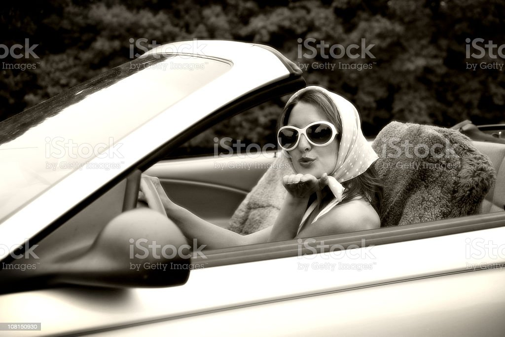 Woman Blowing Kisses From a Convertible royalty-free stock photo