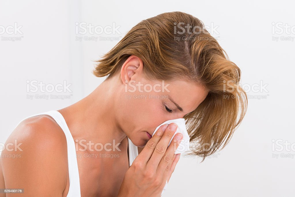 Woman Blowing Nose In Tissue Paper stock photo