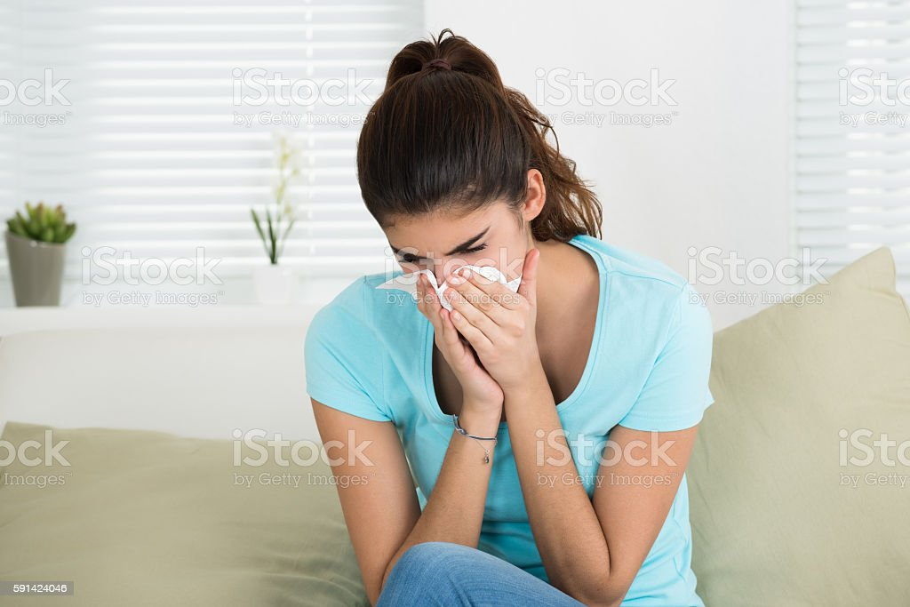 Woman Blowing Nose On Sofa At Home stock photo