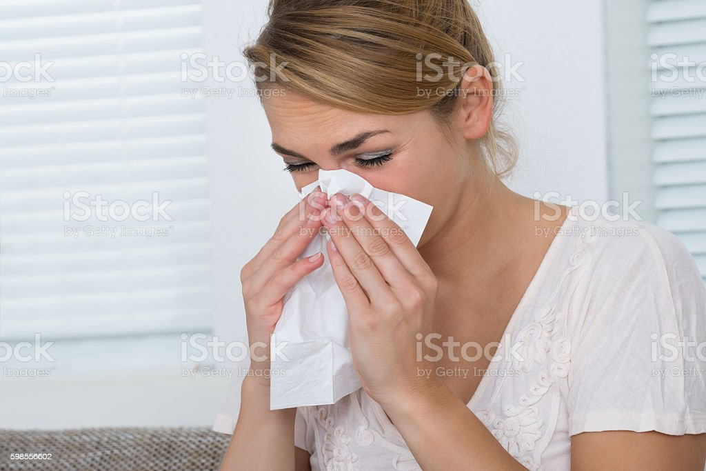Woman Blowing Nose While Suffering From Cold stock photo