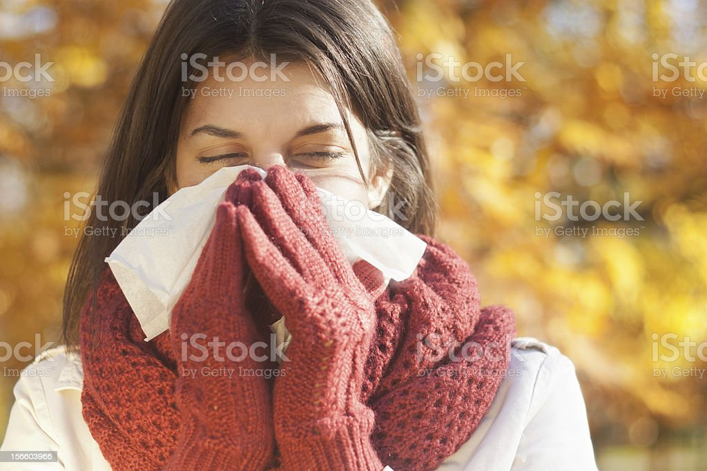 Woman blowing nose with tissue during fall allergy season stock photo