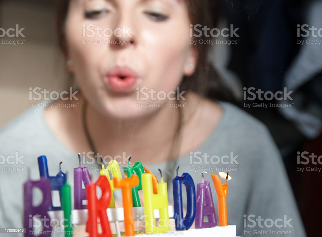 Woman blowing out candles on birthday cake royalty-free stock photo