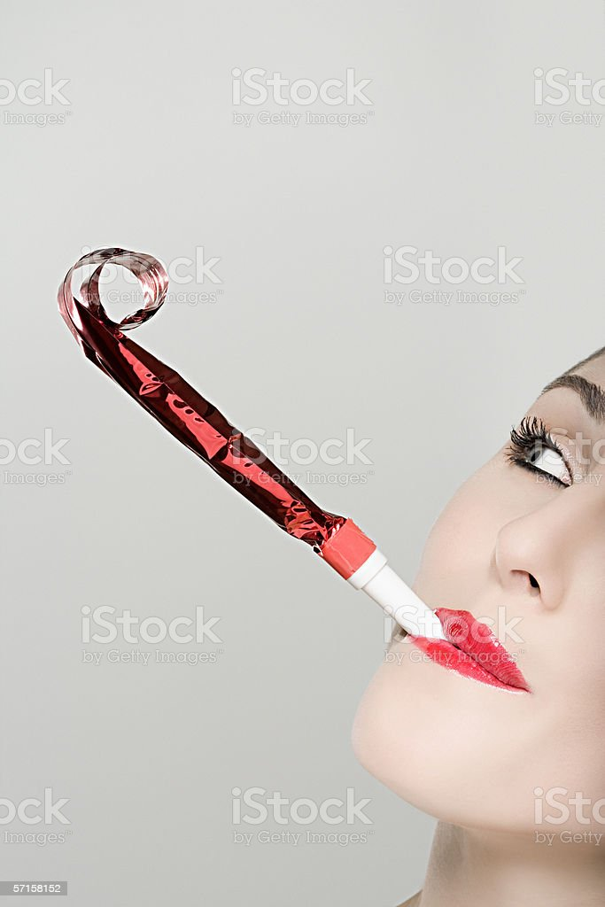 Woman blowing party horn blower stock photo