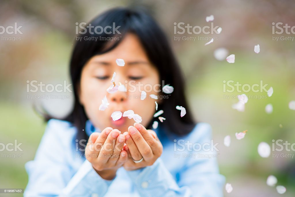 Woman blowing petals out of her hands stock photo