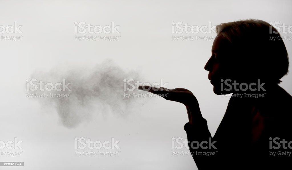 woman blowing powder stock photo