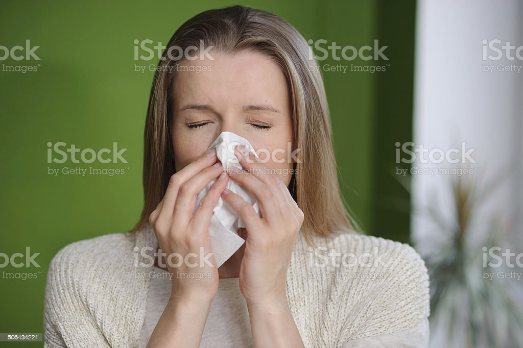 Woman blowing runny nose - Cold flu illness stock photo